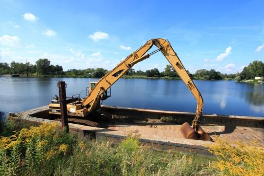 Koparka hydrauliczna czerpakowa CAT na pontonie dolnopokładowym.